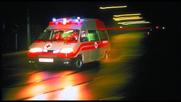 Ein RK-Rettungswagen im nächtlichen Einsatz mit Blaulicht. Bild wurde in RKZ als Hintergrundmotiv verwendet, auch Titelbild des Erste-Hilfe-Kursbuches. Querformat.